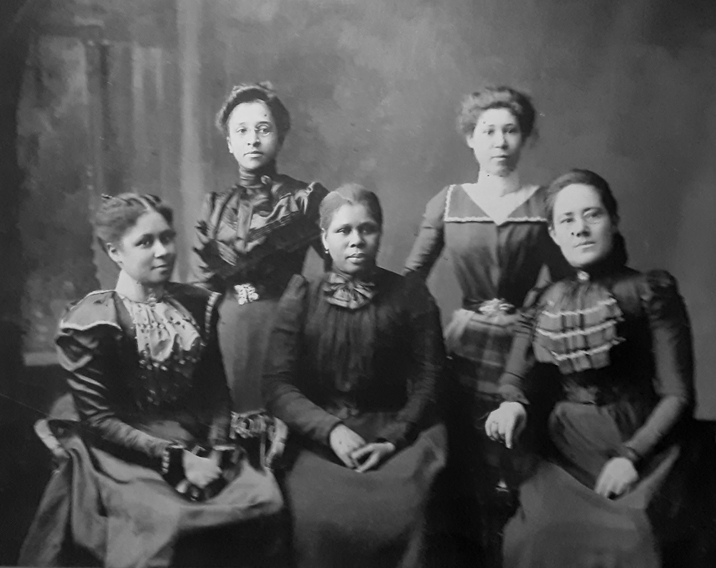Five black women sitting in nineteenth-century clothing