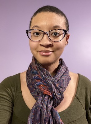 A head and shoulders portrait of Amber Harrison, a young African American woman. She has very short hair and wears glasses. She is wearing a green top accessorized with a purple scarf.