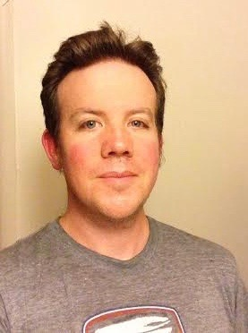 A head and shoulders picture of Andrew Wilhelm, a Caucasian man with short brown hair and no facial hair. He is wearing a gray t-shirt and a slight smile.
