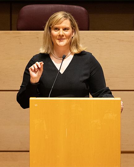 Angie Povilaitis speaks at a podium