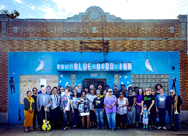 A group of people are pictured in front of a worn, old building with a sign that says The Blue Bird Inn.