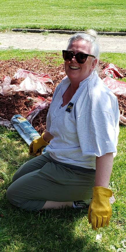 WSU Social Work Associate Professor Carolyn Dayton spreading mulch at the F.A.R.M. offices