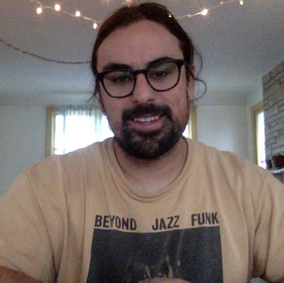A head and shoulders image of Christopher Calandro, a Caucasian man with dark brown hair and beard. He is wearing a faded yellow t-shirt that says Beyond Jazz Funk and dark rimmed glasses.