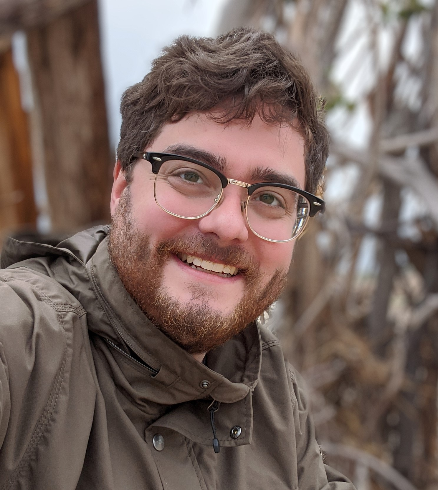 Dave is pictured wearing a brown coat in front of a backdrop of trees. He is a caucasian man with short wavy brown hair and full facial hair. He is wearing glasses and a broad smile.