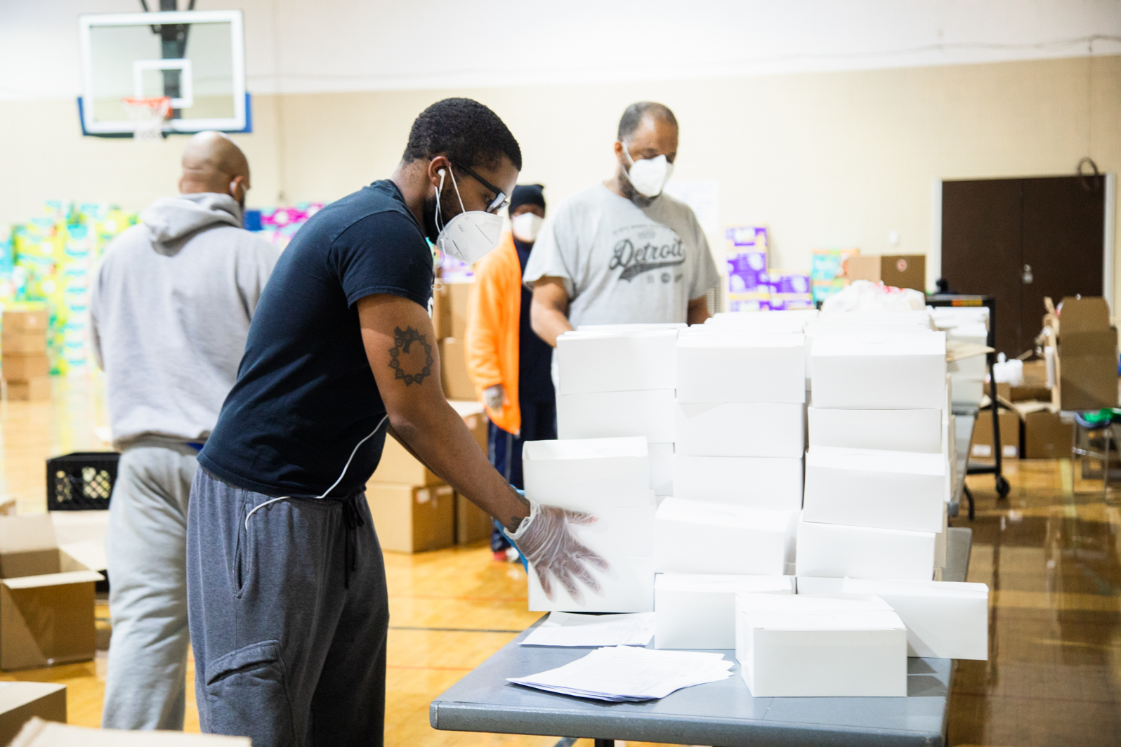 a black man wearing a mask stacks food boxes in a gymnasium