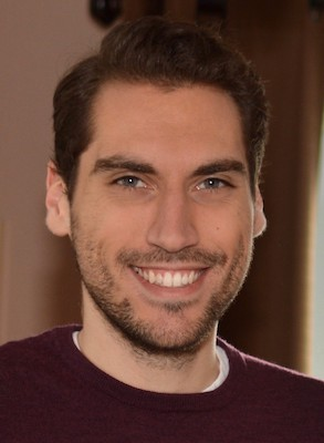 A headshot of Eric Morgal, a Caucasian man with dark brown hair and slight beard. He is wearing a burgundy colored sweater and a large smile.