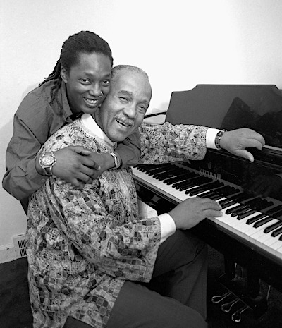A Black man with graying hair and mustache sits at a piano. His wife, a Black woman with dreadlock hair stand behind him with her arms wrapped tightly around him. They are both smiling joyfully and lovingly as they look toward the camera.