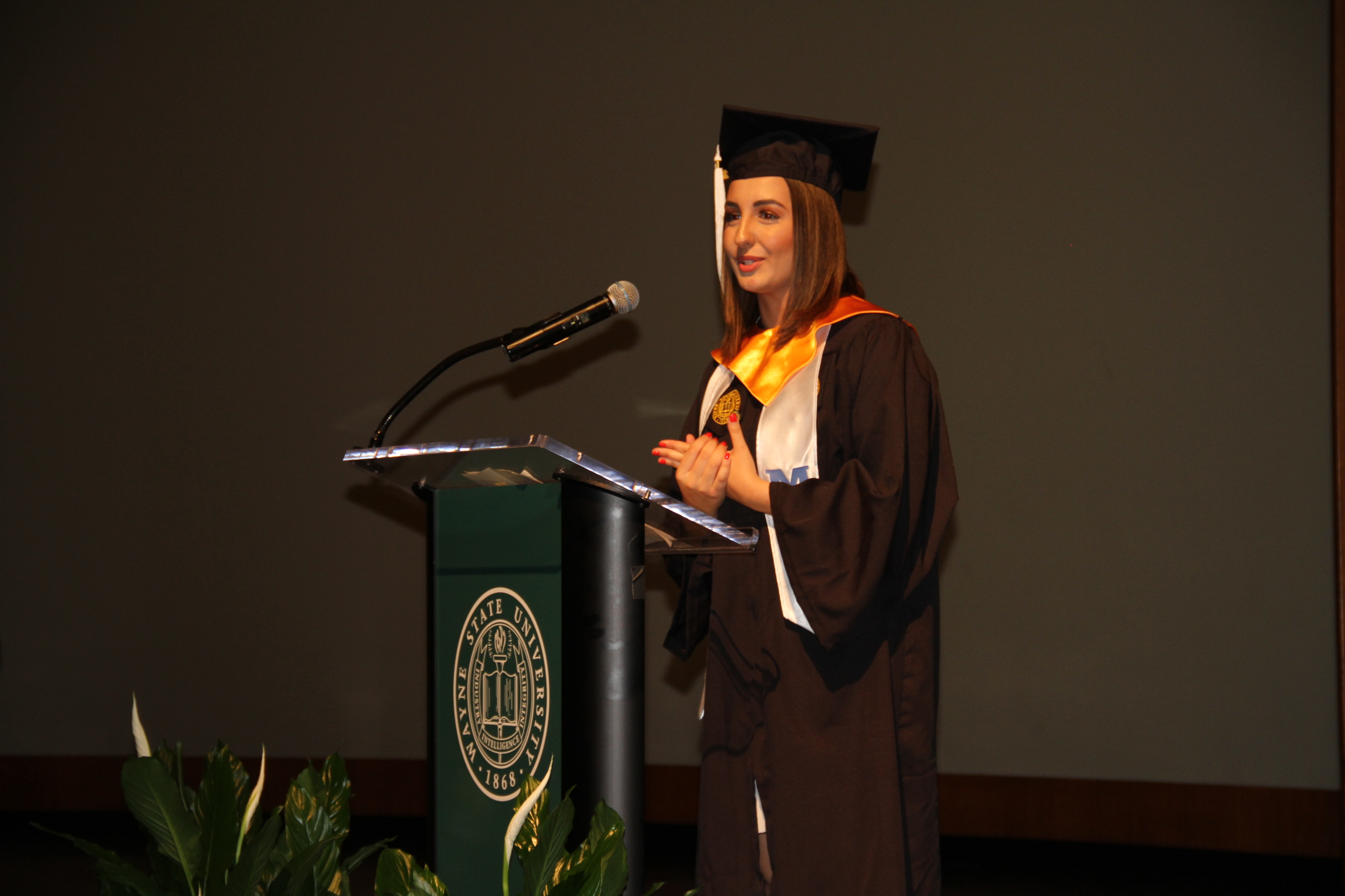 Laial Beidoun speaking at podium in cap and gown