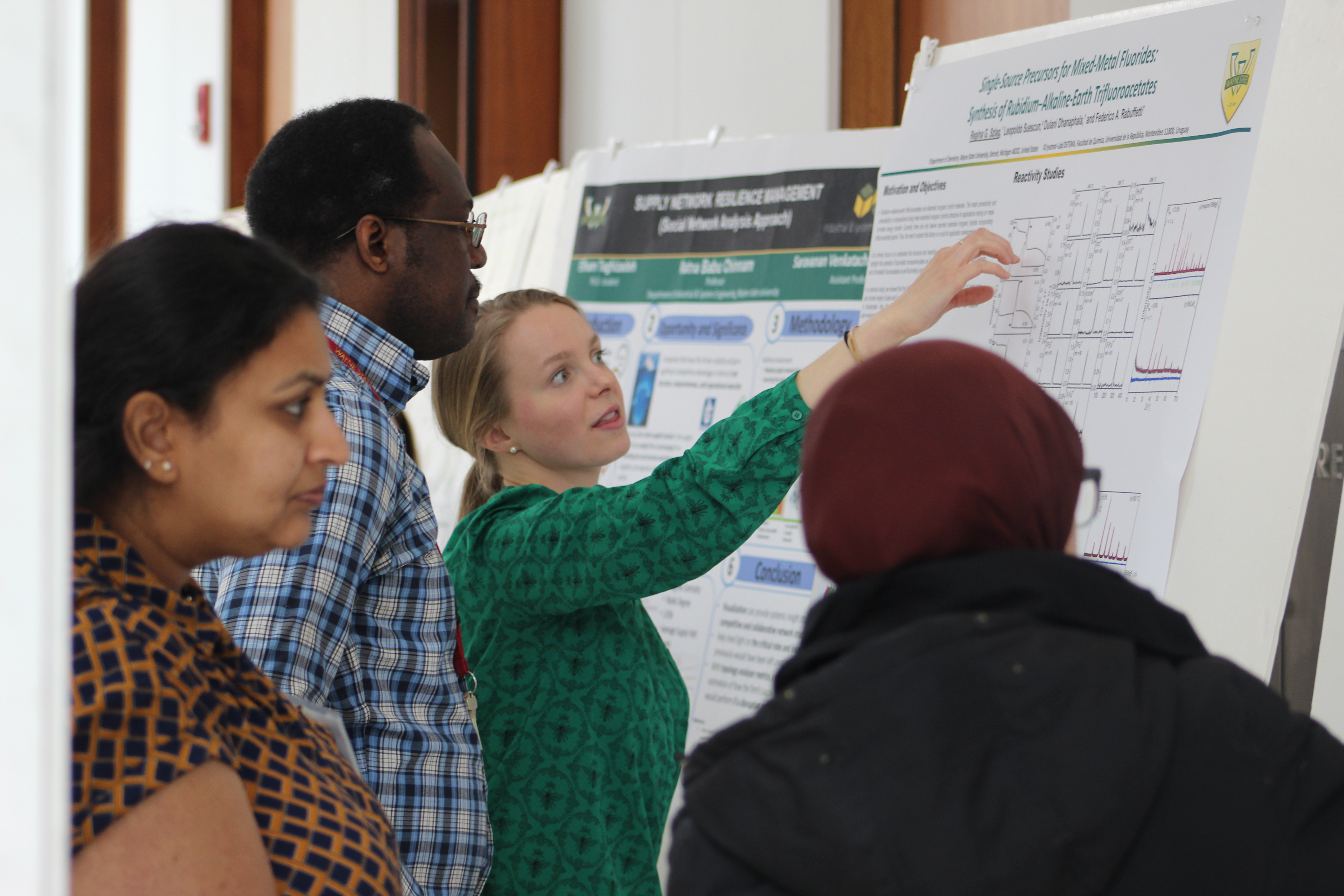 a student showcases her research poster at the graduate research symposium