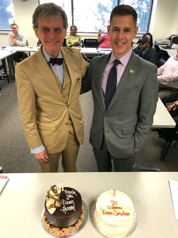 Two men standing in front of cakes during a celebration.
