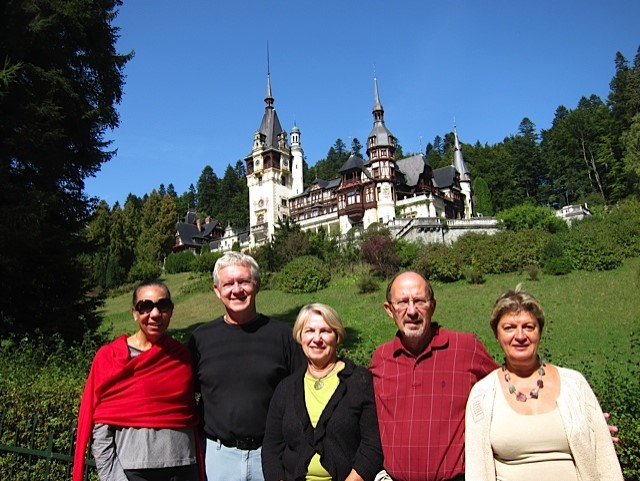A group of travelers in Romania are pictured in front of a castle-like building