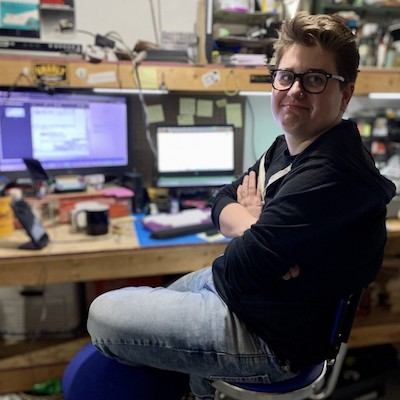 Leah Minadeo is a caucasian woman with short hair and glasses. She is pictured in front of a work station with several computer monitors. Her arms and legs are crossed and she is wearing jeans and a dark colored hooded sweatshirt.