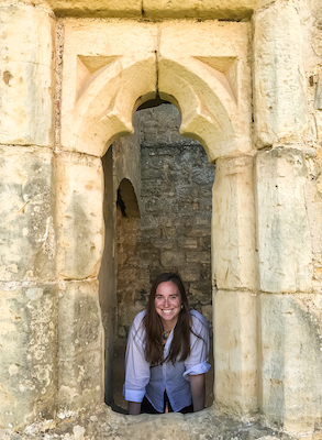 Leigh Holmes, a caucasian woman with long, light brown hair, is posted in the open window of an ancient looking building. She is wearing a white button-up shirt that is rolled up at the sleeves.