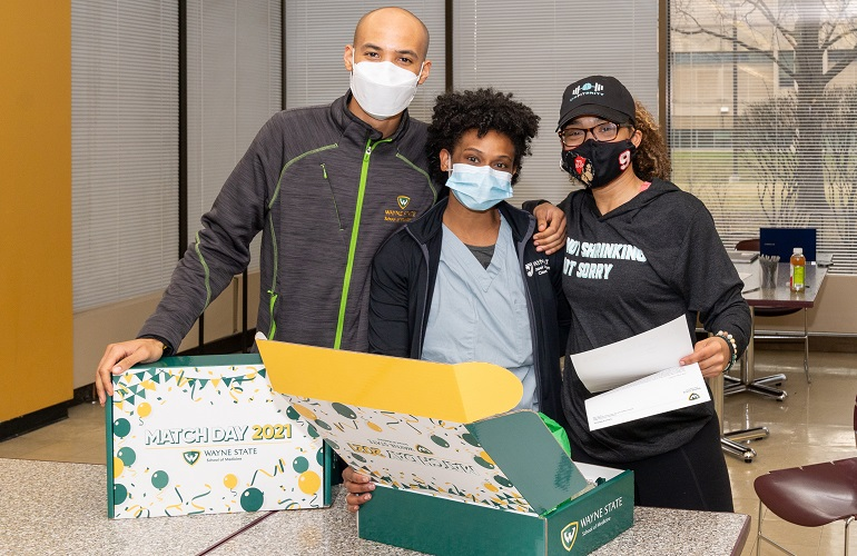 Three students posing with Match gift box at the School of Medicine