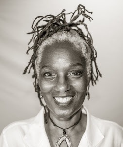 A black and white headshot of McKinney, a Black woman with natural gray hair framing her face. It is pulled back away from her face with thin dreadlocks piled on top of her head. She wears a white collard shirt and a necklace with a large oblong pendant.