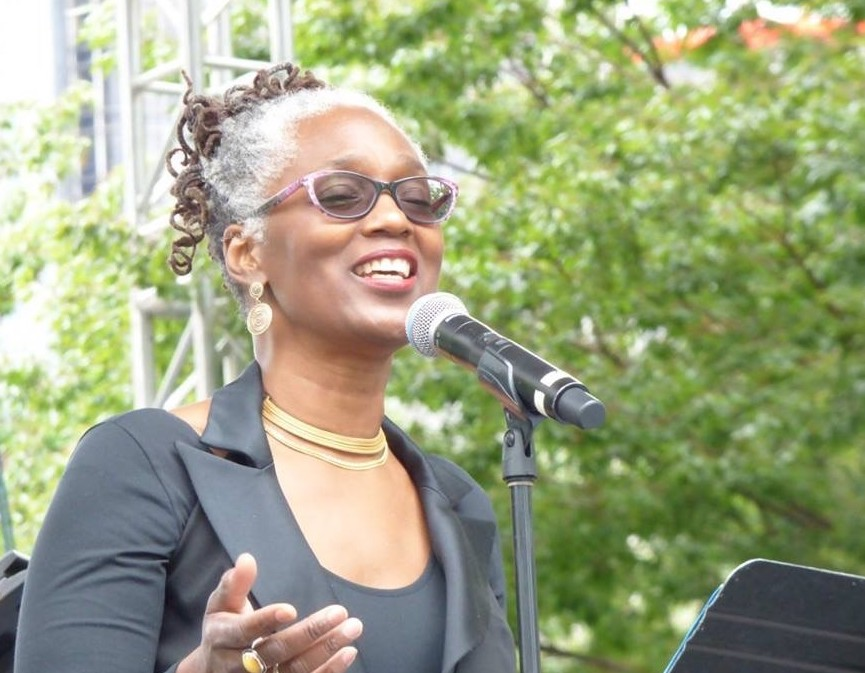 McKinney is singing into a microphone at an outdoor venue. She is a Black woman wearing glasses, a gold choker necklace, gold earrings and a smart black jacket. White hair frames her face and is pulled up to reveal dark curls piled on top of her head.
