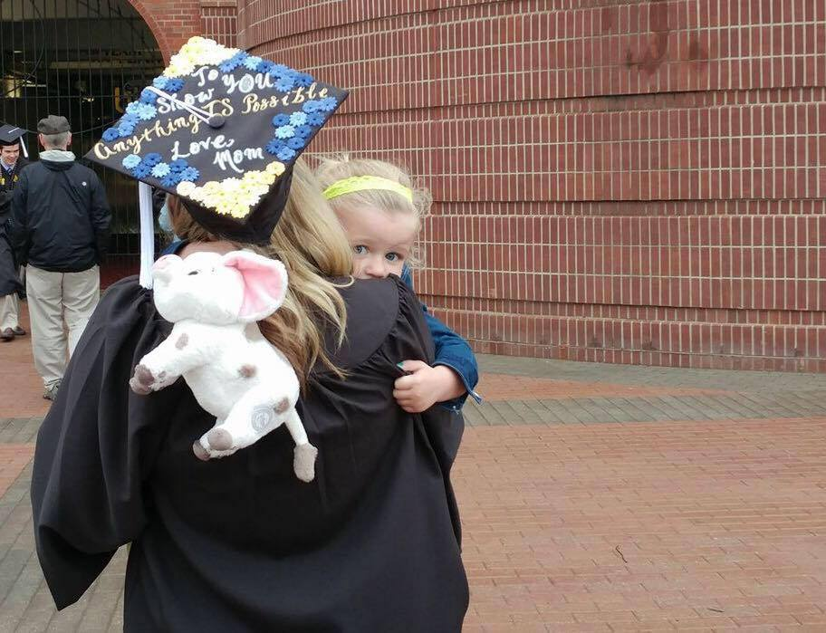 megan antosh on her graduation day with her daughter on her shoulder