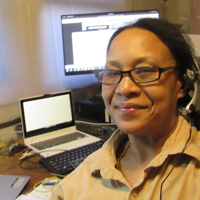 Kendra, an African American woman takes a selfie in front of dual computer monitors. She is wearing glasses, headphones and a slight smile.