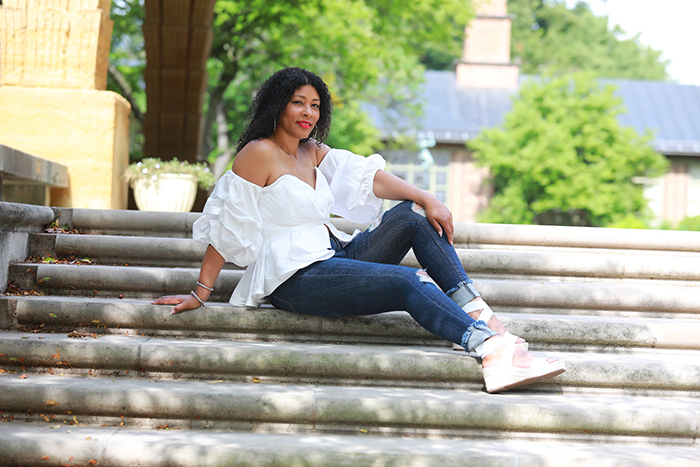 Nikki Wright, smiling, sitting on steps with white shirt and blue jeans