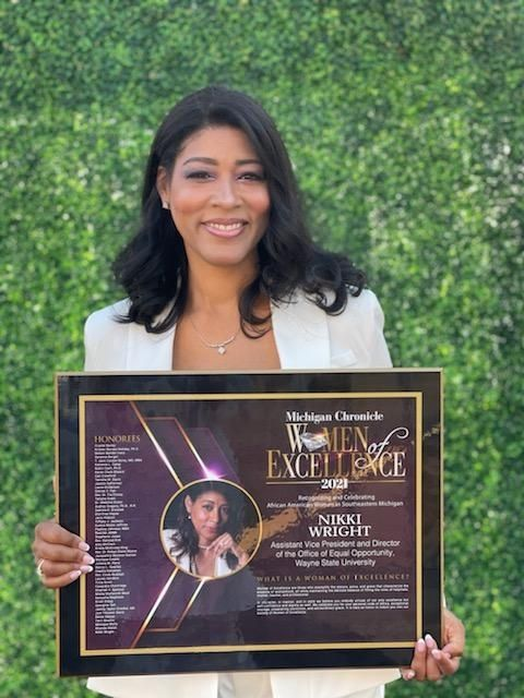 Nikki Wright holding her Women of Excellence award