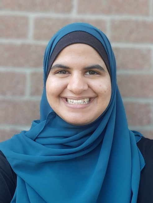 Saba is an Arab American woman pictured in front of a brick wall. She is wearing a teal blue head scarf and a wide smile.