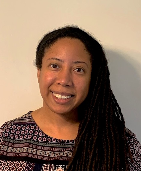 Sarah is a Black woman with long dark hair that is twisted into spirals. She is wearing a printed top and is smiling at the camera.