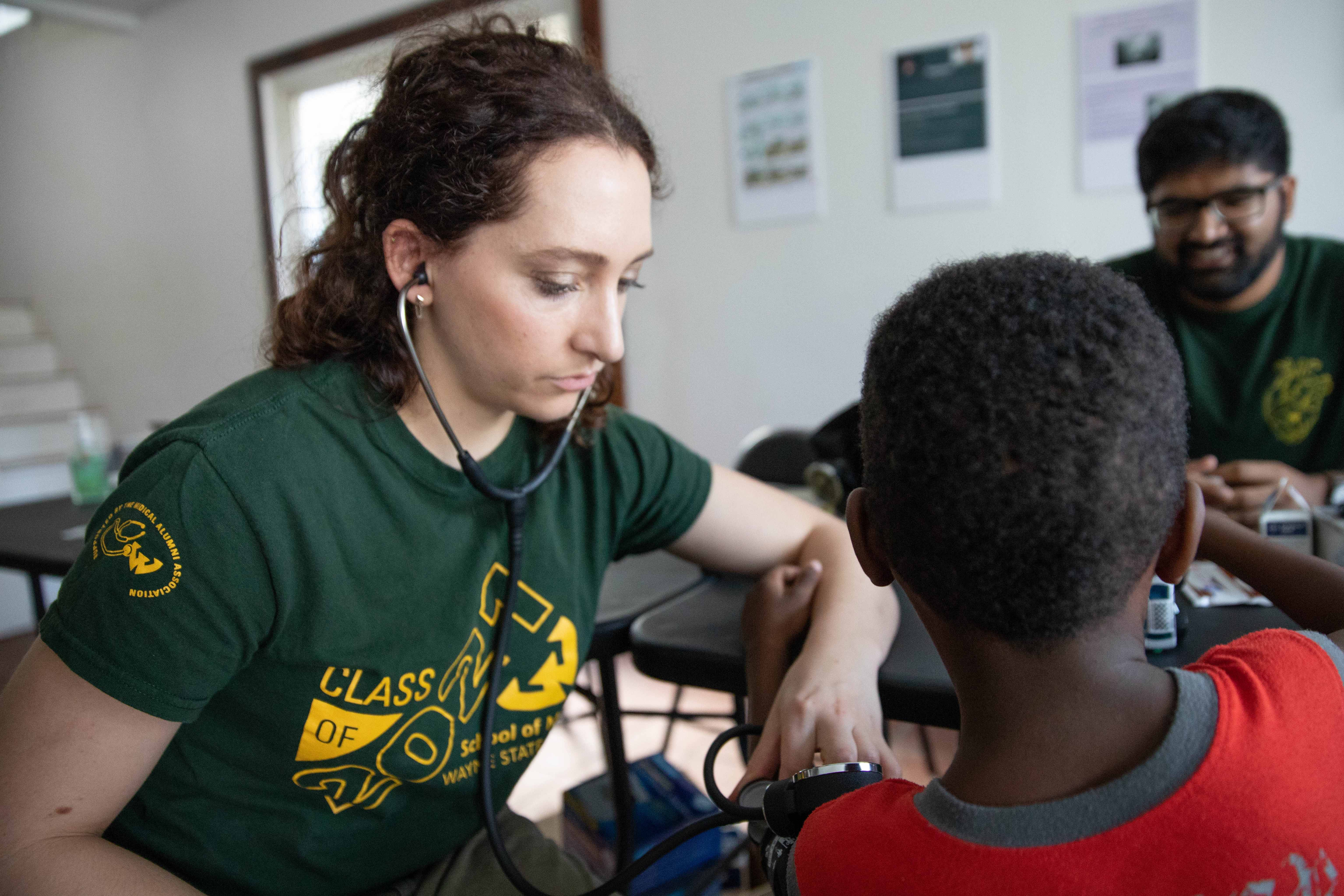 Medical students perform blood pressure check on child