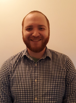 A head and shoulders photo of Thomas Mazza, a Caucasian man with red hair and a closely cropped beard. He is wearing a black and white checked button-up shirt.