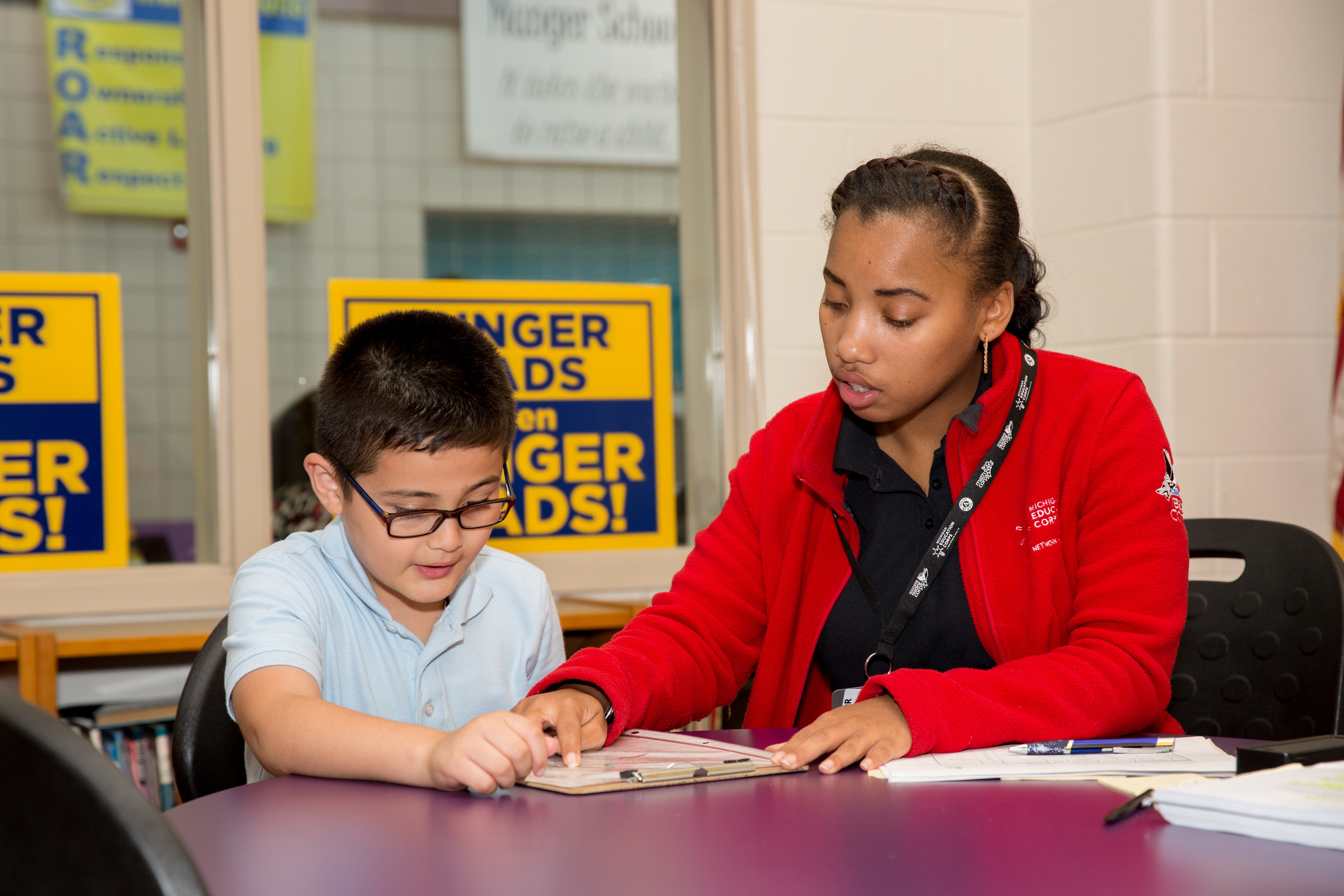 A tutor helps a young student to read