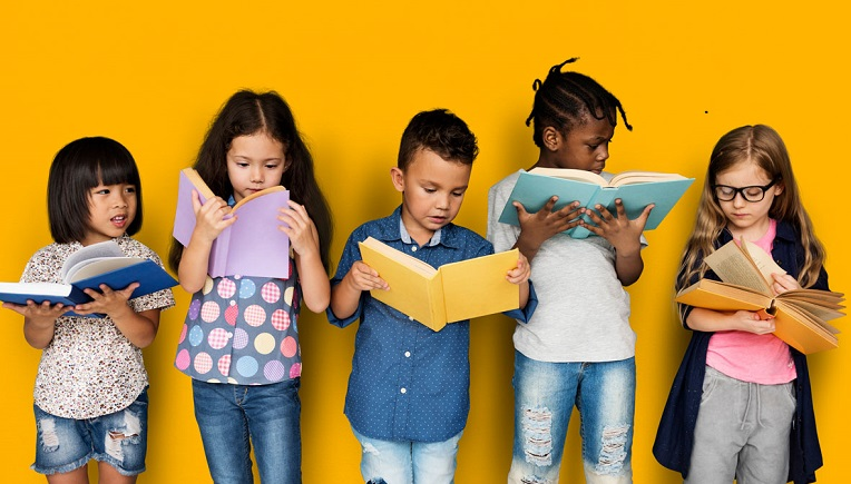 Children against yellow wall reading